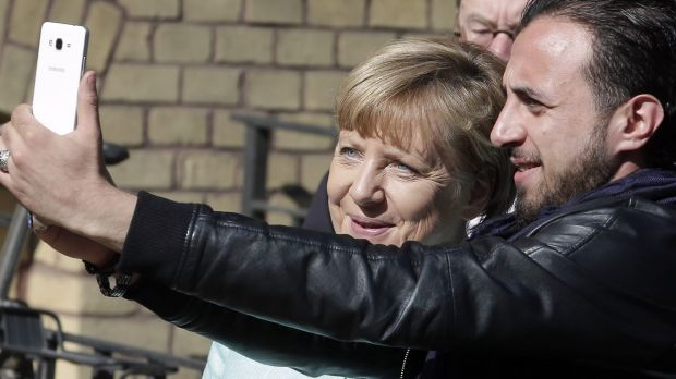An unidentified man takes a picture of himself and German Chancellor Angela Merkel, left, during Merkel's visit to a ...