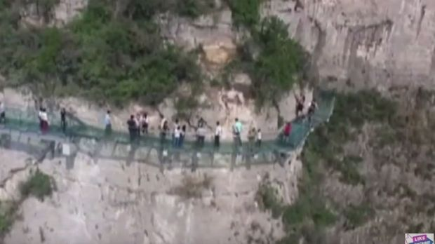 Tourists walking along the new glass walkway at Yuntai Mountain.
