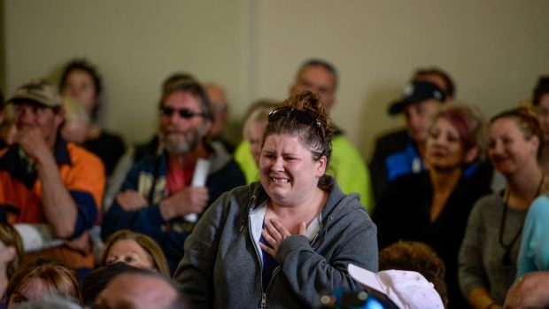 An emotional woman inquires about the status of her house and pets at a community meeting in Lancefield.