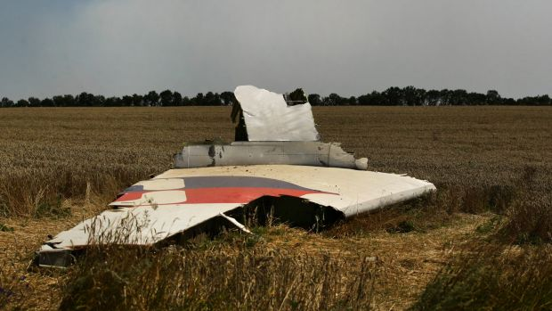 A portion of the MH17 wing lies in the field as smoke rises behind the tree-line. Russians no longer know what to think.