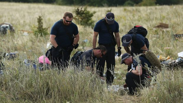 Australian Federal Police officers and their Dutch counterparts collect human remains from the MH17 crash site in the ...