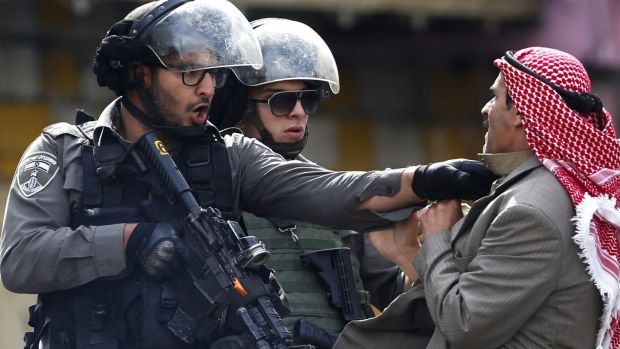 A Palestinian is pushed by Israeli policemen amid clashes in Hebron, West Bank, after a Palestinian teenager stabbed two ...