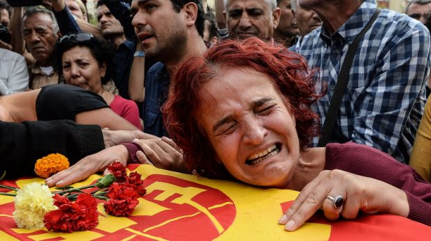 Family members of Korkmaz Tedik, a victim of bomb blasts on October 10, mourn over his coffin during a funeral ceremony ...