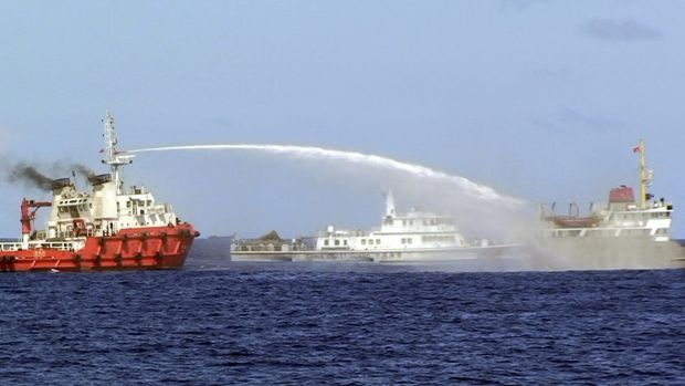 A Chinese ship sprays water on a Vietnamese vessel, right, while a Chinese Coast Guard ship, centre, sails alongside in ...