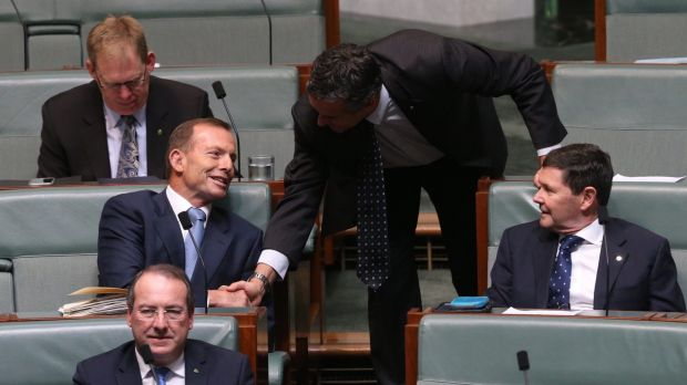Backbencher Tony Abbott is welcomed by Darren Chester during question time at Parliament House.