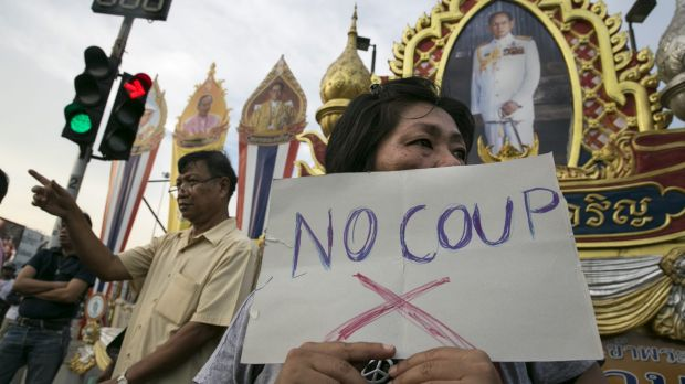 Protesters next to portraits honouring Thai King Bhumibol Adulyadej during anti-coup demonstrations in Bangkok in May ...