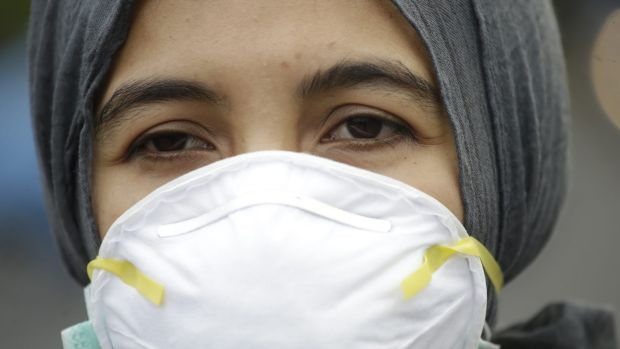 An Indonesian activist wears a mask during a protest demanding the government take quick action to suppress the haze ...