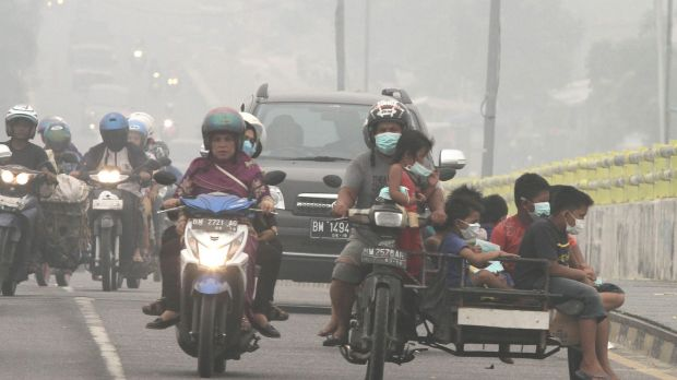 Motorists ride on a road as thick haze from wildfires blankets the city of Pekanbaru, Riau province, Indonesia, earlier ...