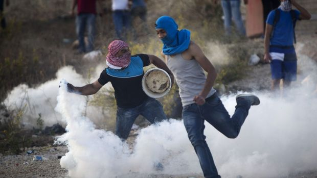 A Palestinian protester throws back a tear gas canister that was fired by Israeli troops during clashes near Ramallah, ...