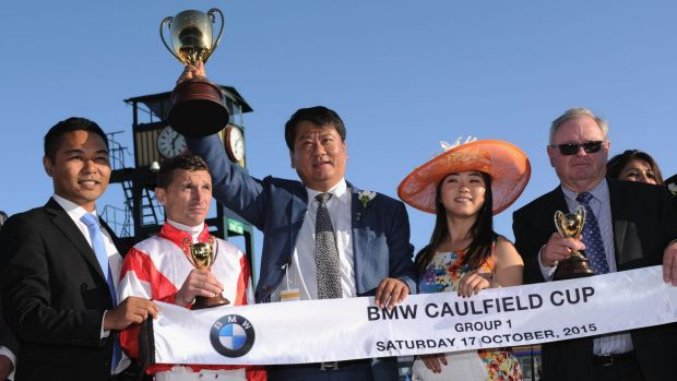 Winning owner Lin Lang poses with the trophy  and jockey Opie Bosson after Mongolian Khan won the Caulfield Cup.