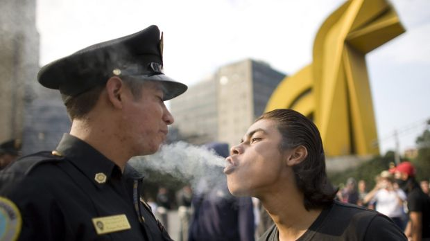 A protester blows marijuana smoke in the face of a police officer in Mexico City.