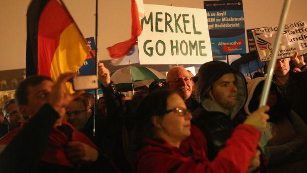 Supporters of the AfD political party protest against German Chancellor Angela Merkel's liberal policy towards migrants ...
