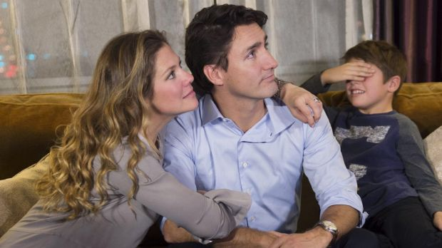 Xavier Trudeau, right, covers his eyes as his dad, Liberal leader Justin Trudeau watches the election results with his ...