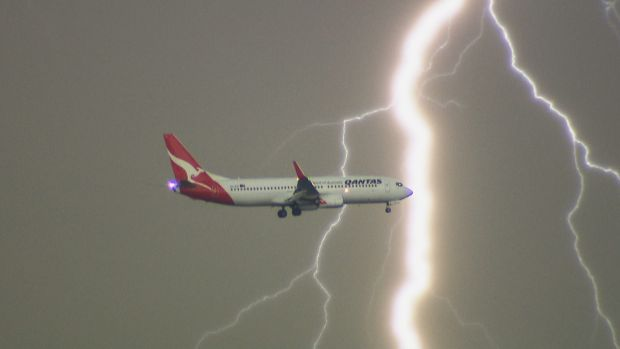 Lightning flashes behind a Qantas plane as it comes in to land in October.
