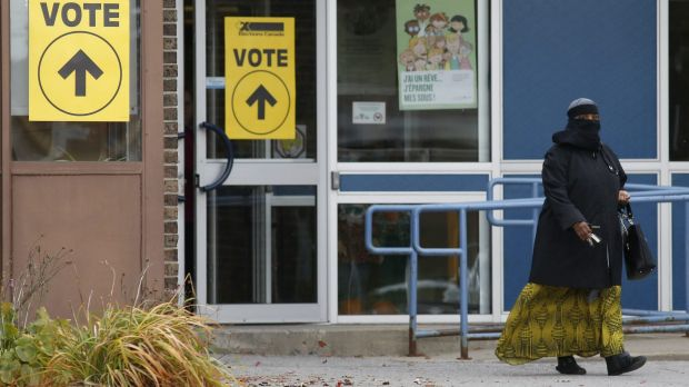 A woman wearing a niqab leaves the Ecole Marius-Barbeau polling station in Ottawa, after casting her vote in the ...