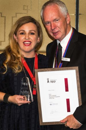 Canberra wedding photographer Kelly Tunney accepting her award from Ross Eason, national president of the Australian ...