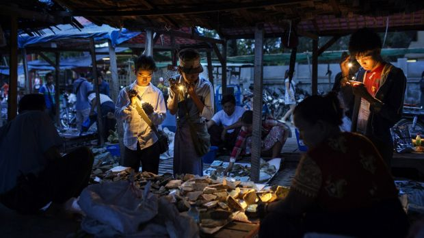 Burmese dealers use flashlights to check the quality of jade at a market in Mandalay, Myanmar last year.