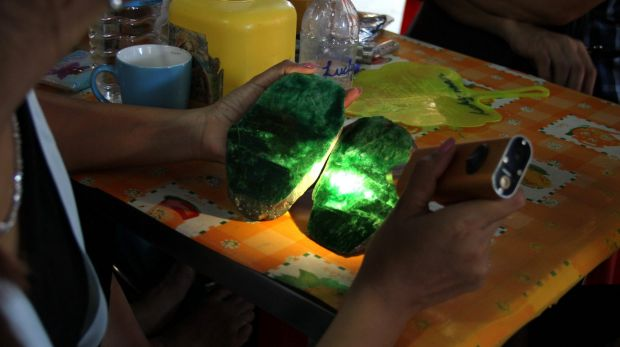 Local people examine the quality of a jade stone in the Hpakant area of Kachin state, northern Myanmar last month.