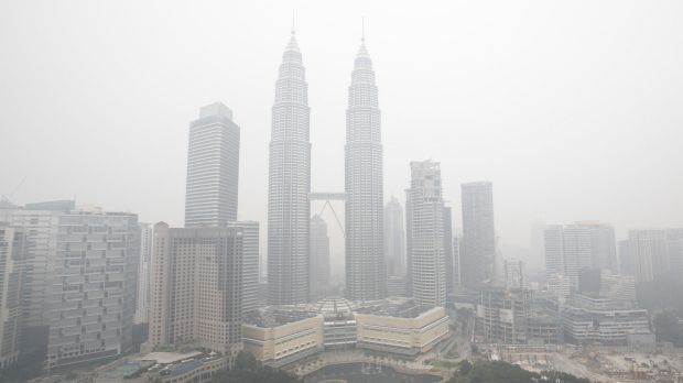 Malaysia's landmark Petronas Towers and other commercial buildings are seen shrouded with haze in the Malaysian capital, ...