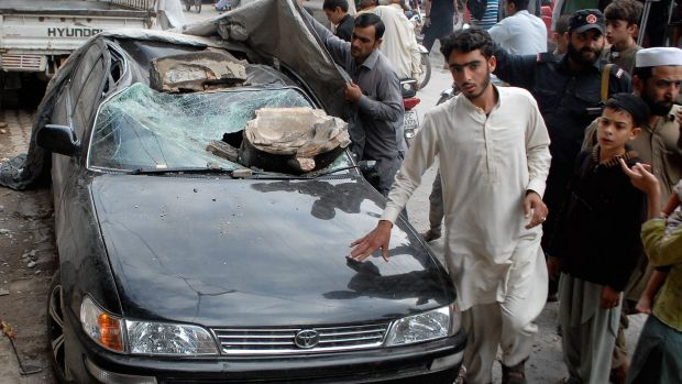 People stand near a car in Peshawar, Pakistan, after Monday's earthquake.