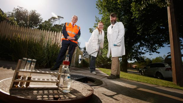 Western Water's Graham Holt, La Trobe University's Elizabeth Mathews and Ashley Franks beside a manhole.