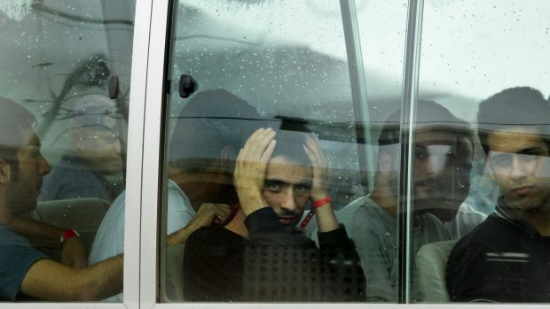 Pezhma Ghorbani (centre,hands on head), 26, from Iran looks out the window of the bus after arriving a plane carrying ...