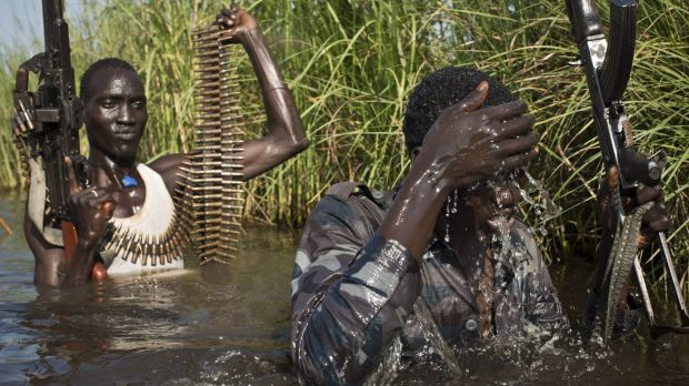 Rebel soldiers walk through flooded areas to reach a UN makeshift camp for displaced people from the Nuer ethnic group ...
