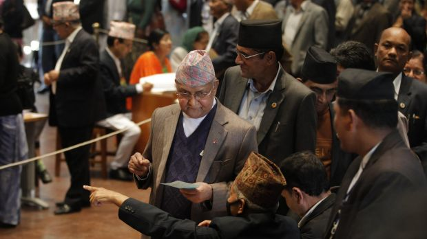 Nepalese Prime Minister Khadga Prasad Oli, centre, prepares to cast his vote as legislators vote for a new president in ...