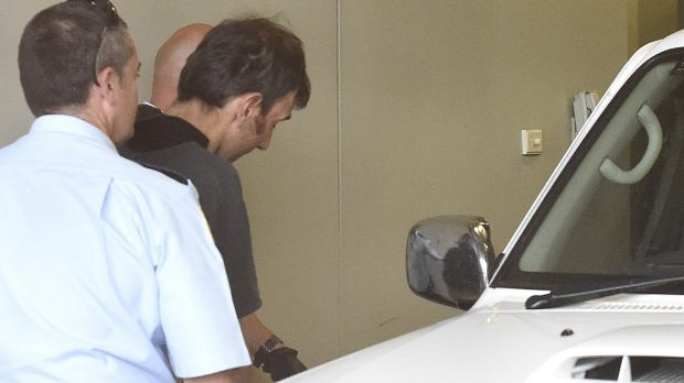 Mark Stocco is led to a prison vehicle after appearing in Dubbo Local Court via video link.