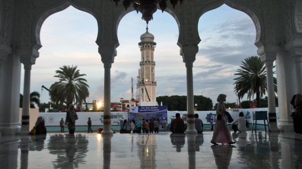 People gather at Baiturrahman Grand Mosque at dusk in Banda Aceh, Aceh province, Indonesia. A local law that makes gay ...