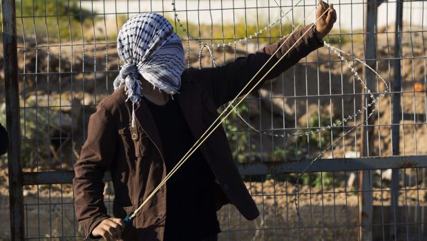 A Palestinian protester stretches a slingshot to hurl a stone during clashes with Israeli soldiers in the northern Gaza ...
