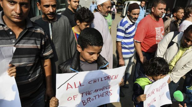 Egyptian boys hold posters to share sorrow outside Zeinhom morgue in Cairo