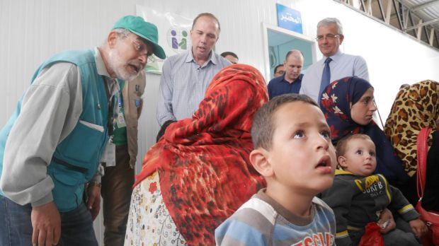 Immigration Minister Peter Dutton talks to a refugee family at a medical clinic at the camp.