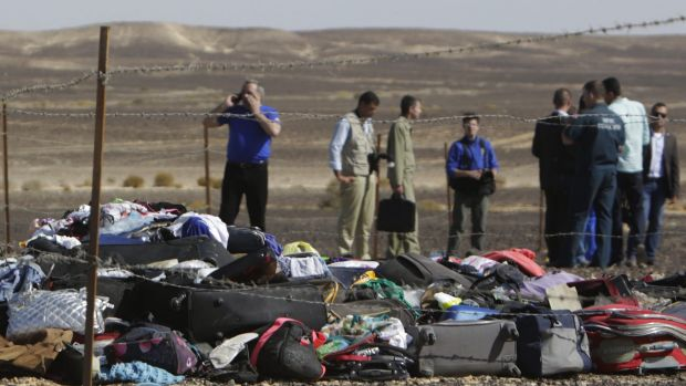 Russian investigators stand near debris, luggage and personal effects at the crash site.