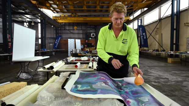 Pickles Auctions floor supervisor Glen Hetherington unrolls a painting 'Yam Flower Dreaming' by Rosemary Pitjara ...