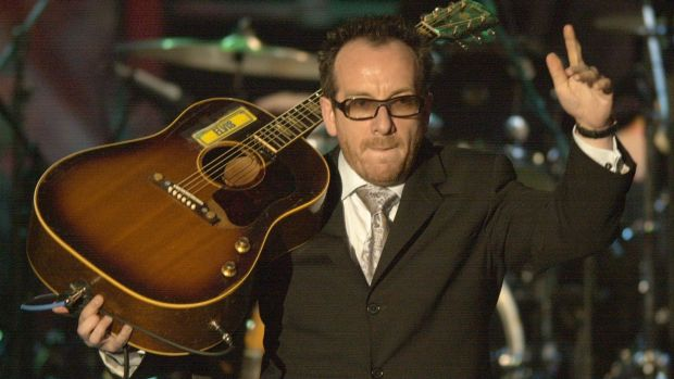Elvis Costello waves to the audience after performing  during the Rock and Roll Hall of Fame induction ceremony in 2003, ...