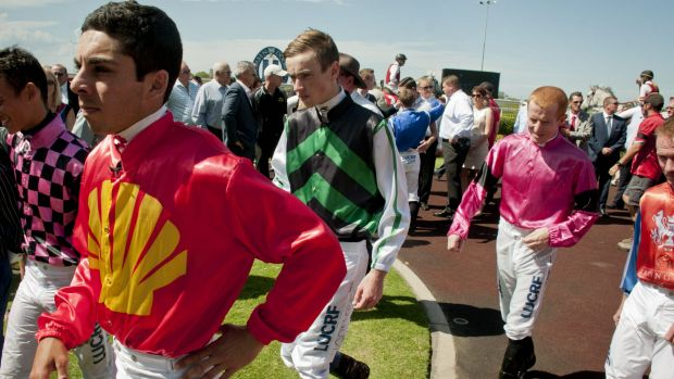 Jockeys gather at the winners area at Doomben racecourse to pay their tributes to Tim Bell with one minute silence.