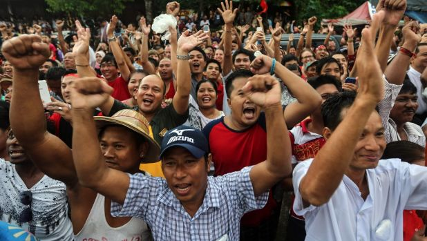 National League for Democracy party supporters cheer as they gather to hear first election results outside the party ...