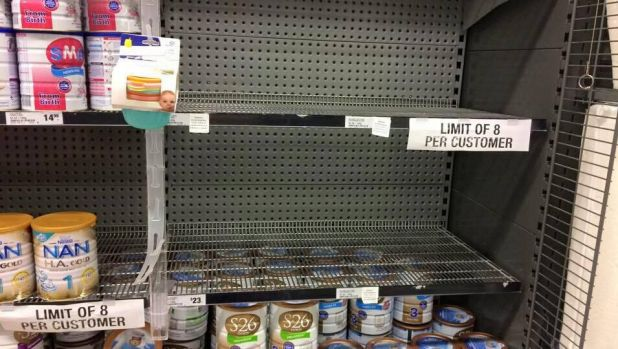 A Woolworths shelf emptied of popular Australian brands. It's imposed an eight-tin limit.