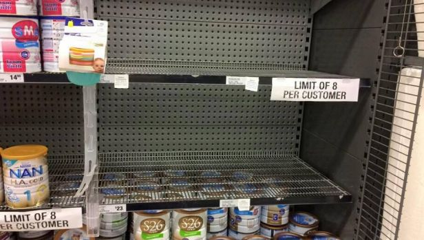A Woolworths shelf emptied of popular Australian infant formula brands. The supermarket has imposed an eight-tin limit.