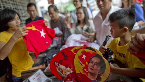People buy merchandise with pictures of Aung San Suu Kyi at a shop run by her National League of Democracy in Yangon.