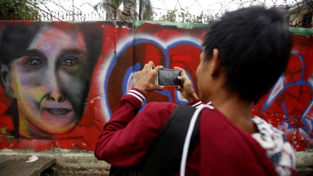 A man takes pictures of graffiti congratulating Myanmar opposition leader Aung San Suu Kyi and her party's victory in ...