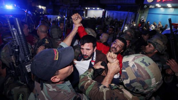 Lebanese soldiers arrest a suspected attacker near the scene of a twin suicide attack in Beirut.