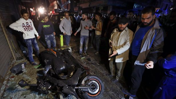 People gather near the site of a twin suicide attack in Burj al-Barajneh, southern Beirut.