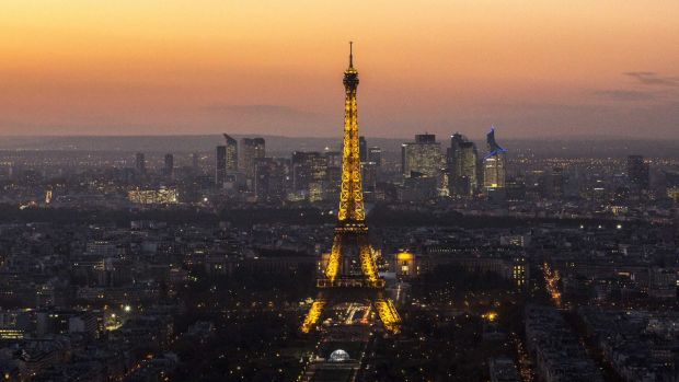 The Eiffel Tower stands illuminated on the skyline, a symbol of Parisians' pride in their city.