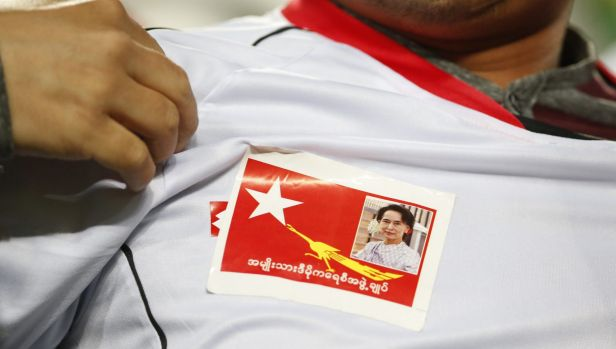 A Myanmar soccer fan shows  a picture of Myanmar opposition leader Aung San Suu Kyi during the country's 2018 FIFA World ...