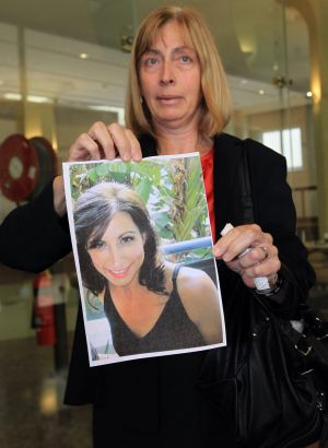 Louise Miller holds a photo of her sister, victim Catherine Pracy.