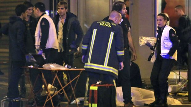 Rescue workers at the scene as victims lay on the pavement outside a Paris restaurant on Friday.