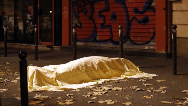 A victim under a blanket lays dead outside the Bataclan theater in Paris.