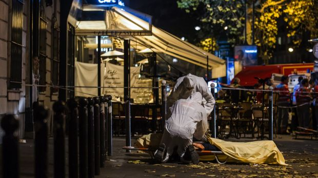 Investigating police officers inspect the body of a victim of the November 13 attacks outside the Bataclan concert hall ...